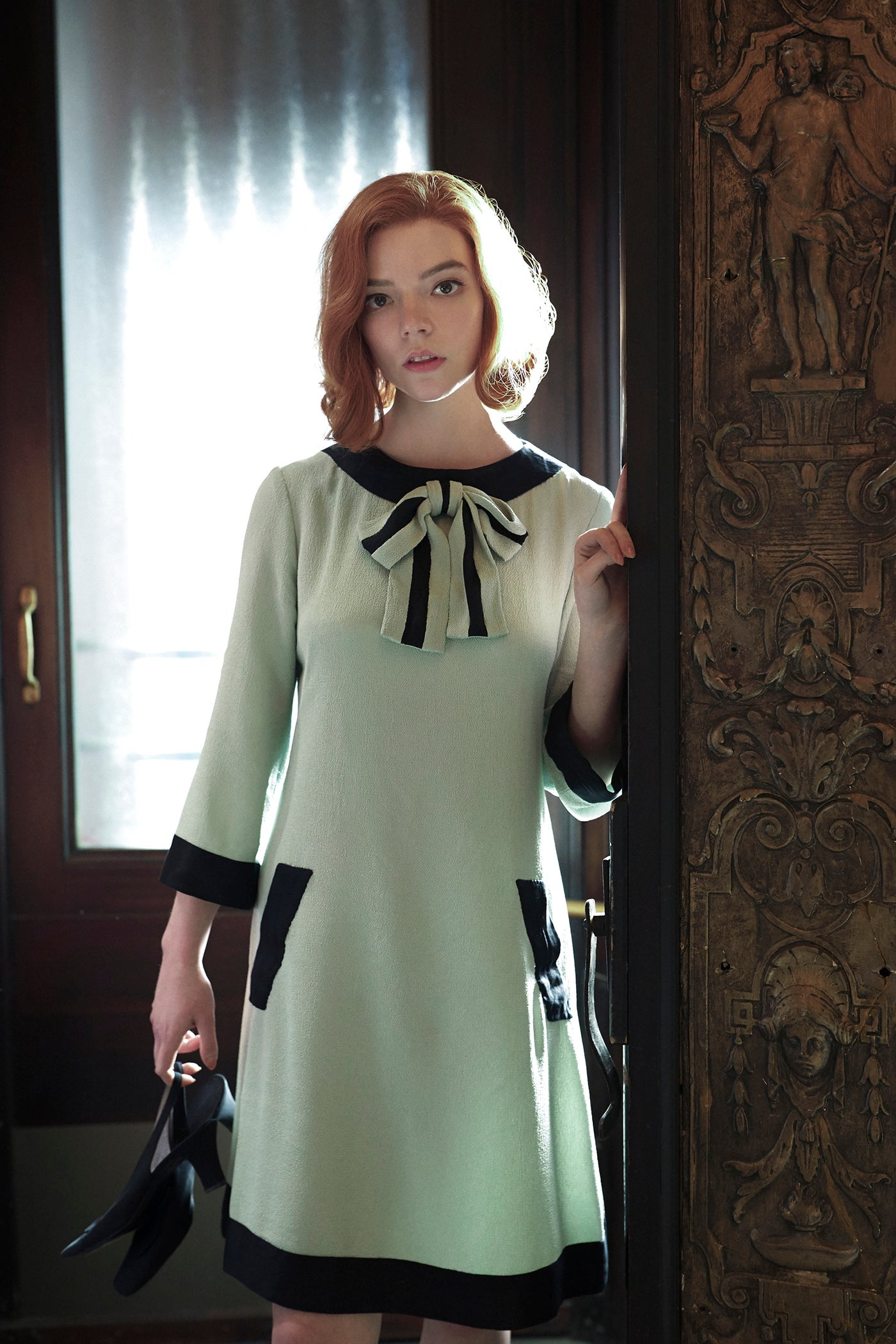 The mint and black bow dress is made from creped viscose, jumping with movement to support her disorderly state.