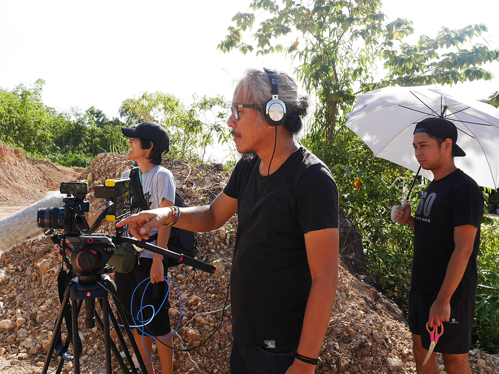 "Cecil Buban (Sound Recordist), Lav Diaz, and Robinne Martillano (Art Director) on the set of ""Genus Pan"" (2020)"