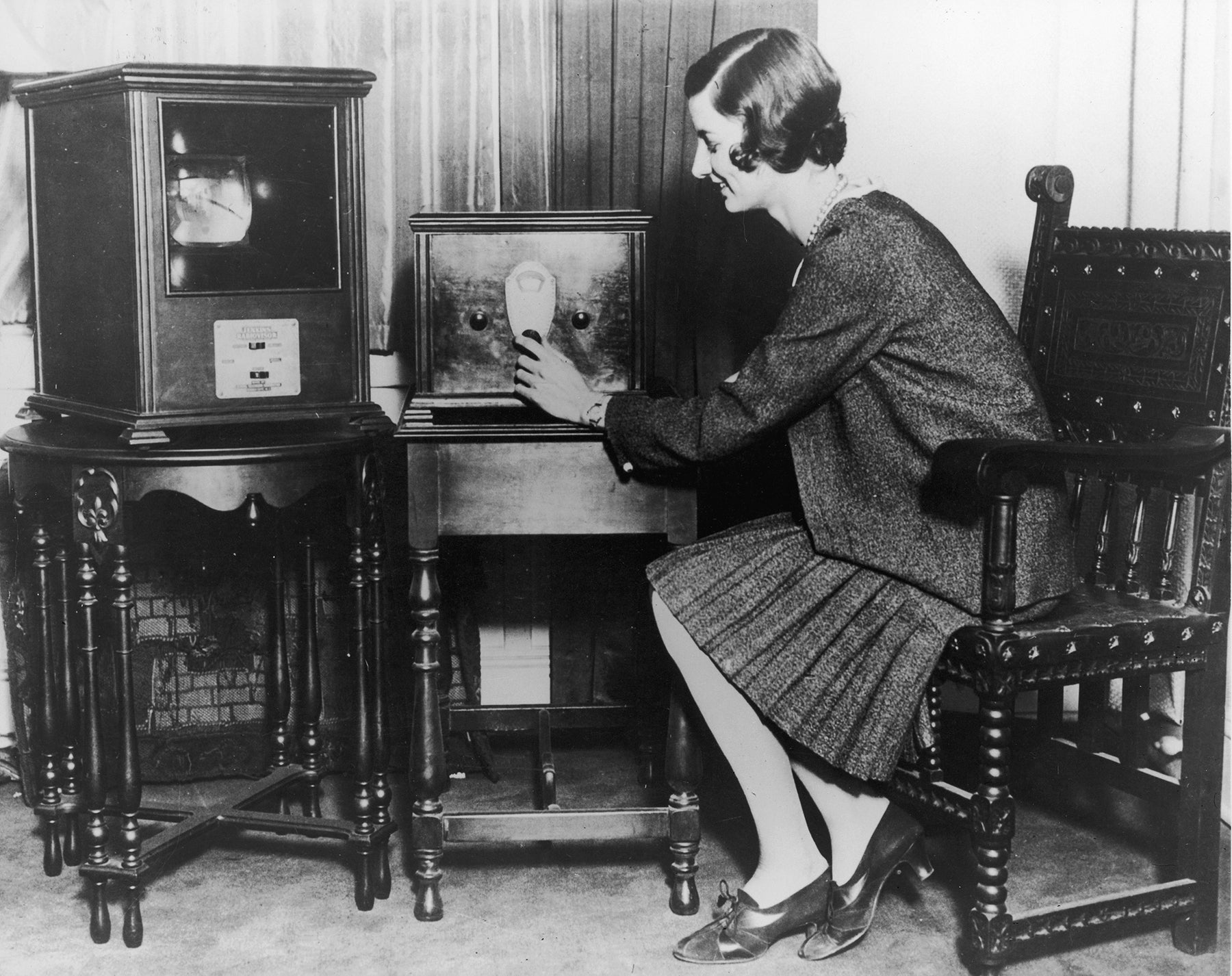 January 30, 1930: A woman smiles while turning the dial of an early television receiver, the Jenkins 'Model 200 Radiovision'.