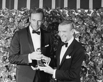 Actor Charlton Heston recieves the Cecil B.deMille Award from Fred Astaire, 1967