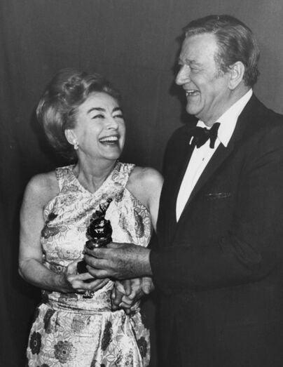 Actress Joan Crawford receives Cecil B.deMille award from John Wayne
