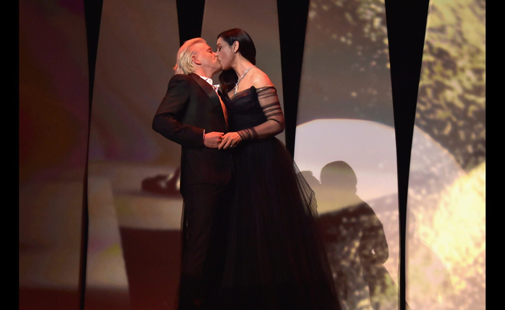 Mistress Of Ceremonies Monica Bellucci (R) and French comedian Alex Lutz kiss during the Opening Ceremony of the 70th annual Cannes Film Festival