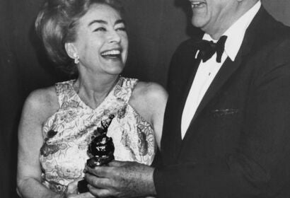 Actress Joan Crawford receives Cecil B.deMille award from John Wayne