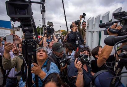 Journalists try to photograph members of a caravan of Central Americans who spent weeks traveling across Mexico as they walk from Mexico onto the U.S. side of the border to ask authorities for asylum on April 29, 2018 in Tijuana, Baja California Norte, Me
