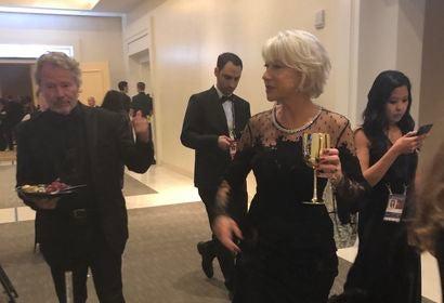 Golden Globes 2018: Helen Mirren backstage with a large gold goblet.